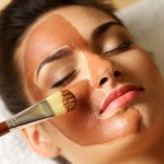 woman while facial cosmetic procedure in spa salon