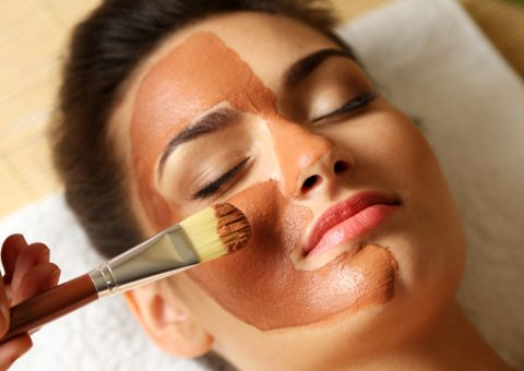 woman while facial cosmetic procedure in spa salon